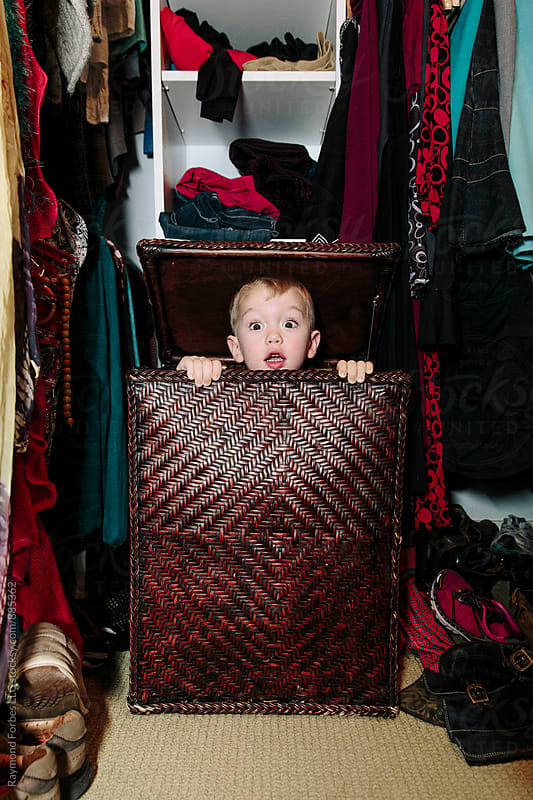 Child Hiding in Laundry Hamper by Raymond Forbes LLC for Stocksy United