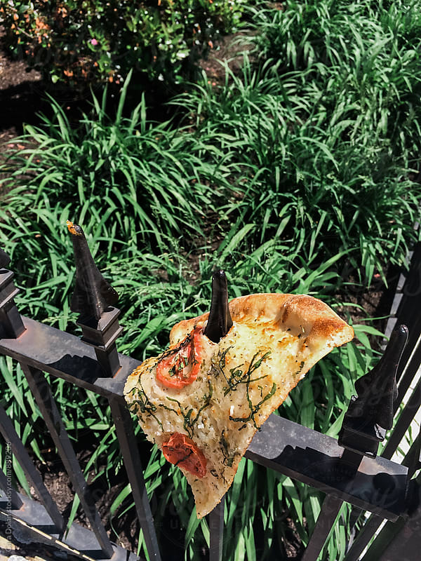 Margherita pizza impaled on iron fence by Cara Dolan for Stocksy United