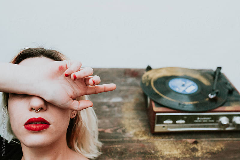 woman covering her eyes near a turntabe by Thais Ramos Varela for Stocksy United