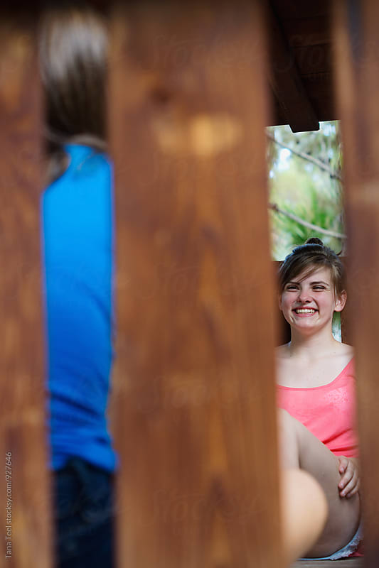 smiling teen sits in play structure with friend by Tana Teel for Stocksy United