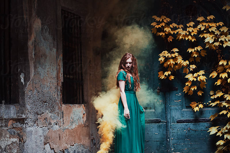 Dreamy portrait of a young woman standing in a yellow smoke by Jovana Rikalo for Stocksy United