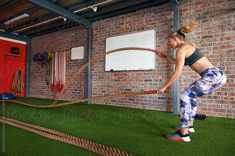 woman doing exercises with ropes at a gym by Daxiao Productions for Stocksy United