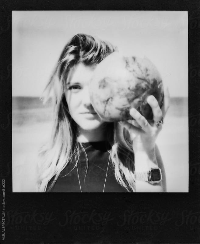 Black and White Polaroid of Young Woman Holding Coconut in Front of Face by Julien L. Balmer for Stocksy United