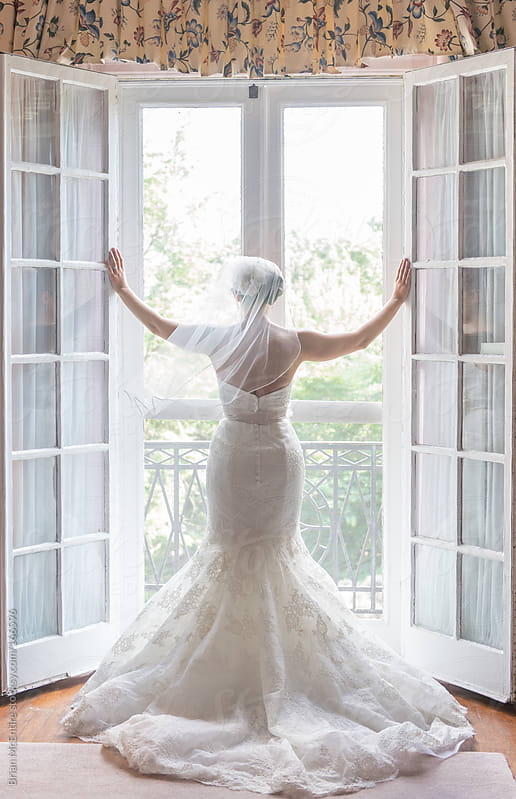 Bride in classic wedding dress looking over balcony through french doors by Brian McEntire for Stocksy United