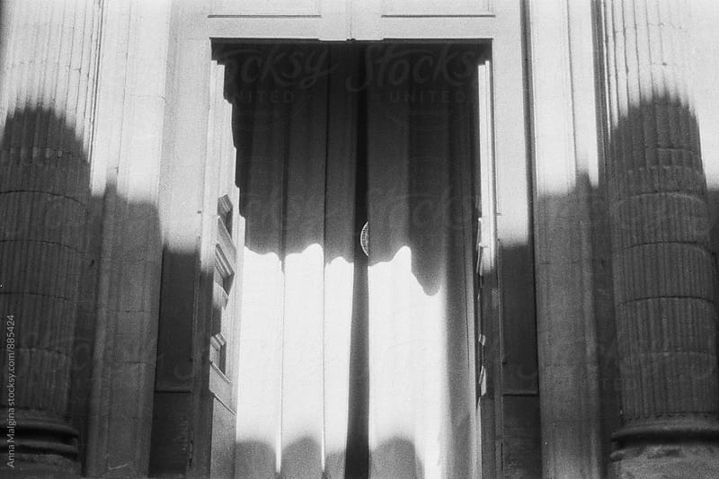 A black and white film photo of shadows on the curtain of italian cathedral by Anna Malgina for Stocksy United