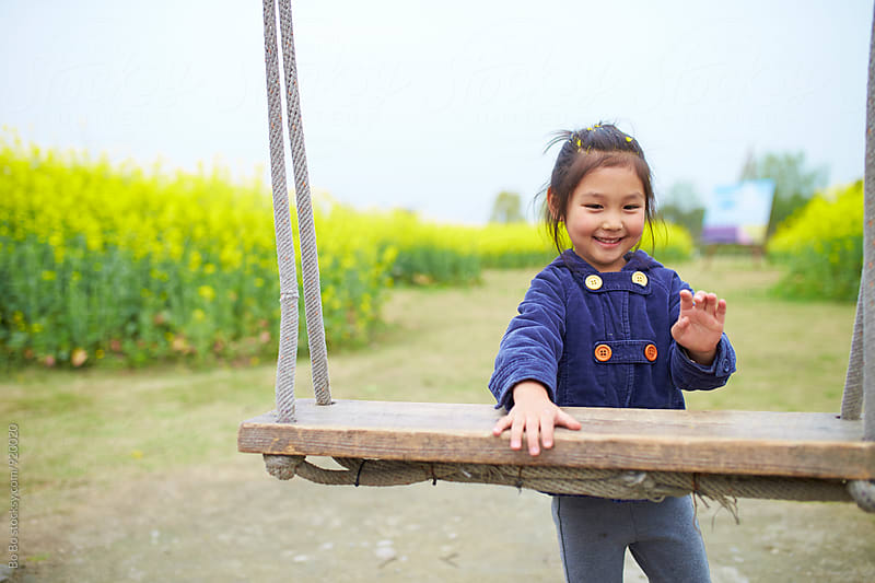 happy little girl playing on the swing by cuiyan Liu for Stocksy United