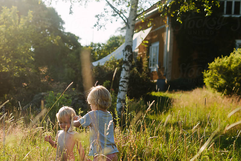 A brother washes his little sister outside in the countryside. by Julia Forsman for Stocksy United