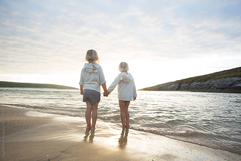 Two sisters at beach watching sunset. by Hugh Sitton for Stocksy United