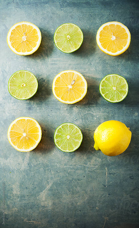 Food: Lemons and Limes Cut in Half with one Full One by Sean Locke for Stocksy United