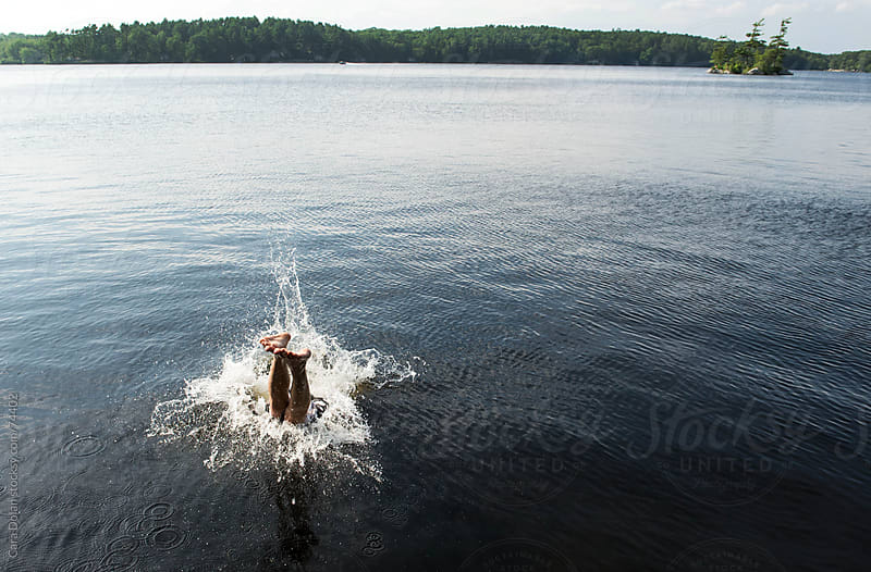 Last glimpse of a man's feet as he dives into lake water by Cara Dolan for Stocksy United