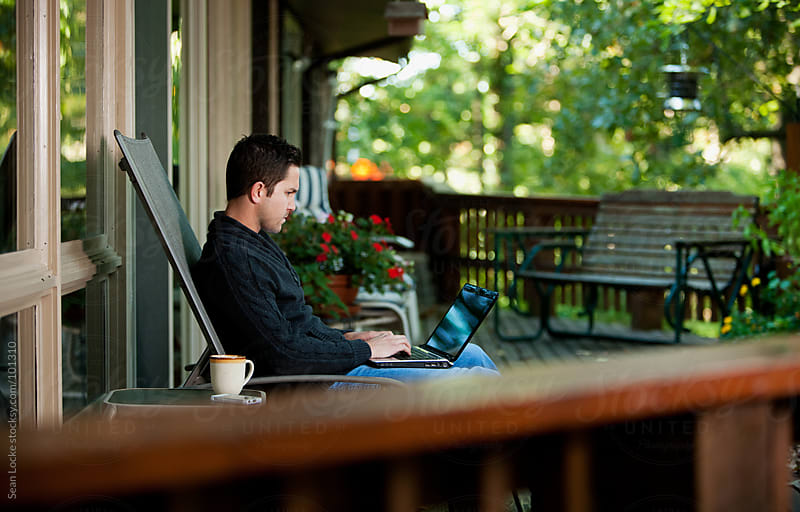 Working: Man Telecommuting With Laptop On Porch by Sean Locke for Stocksy United