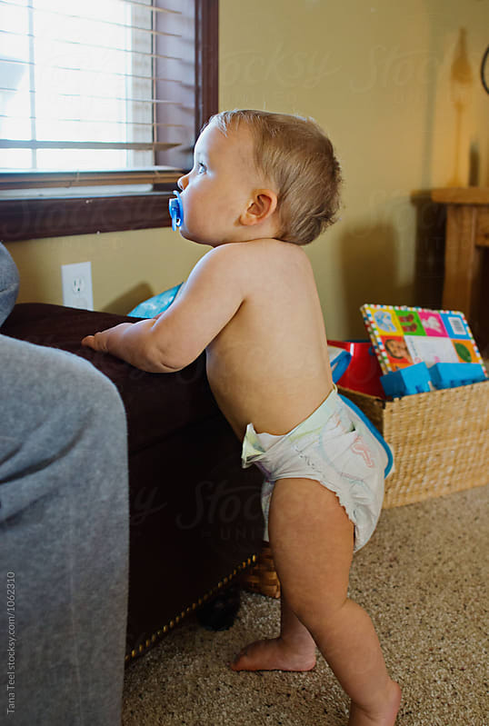 toddler wearing diaper stands looking out window by Tana Teel for Stocksy United