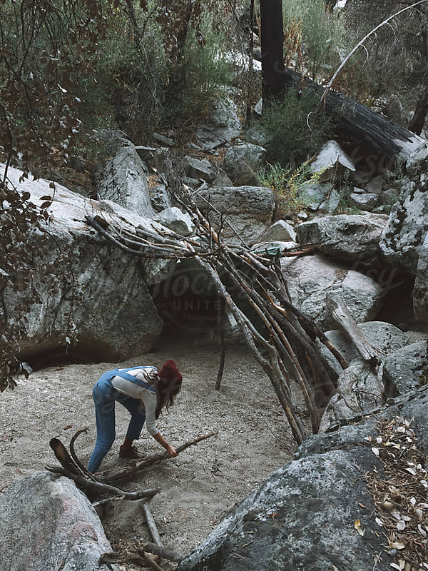 Woman Building a Fort in the Forest by Kevin Russ for Stocksy United