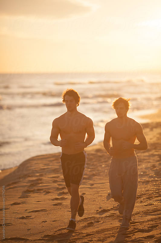 men's couple running at the beach by Leandro Crespi for Stocksy United