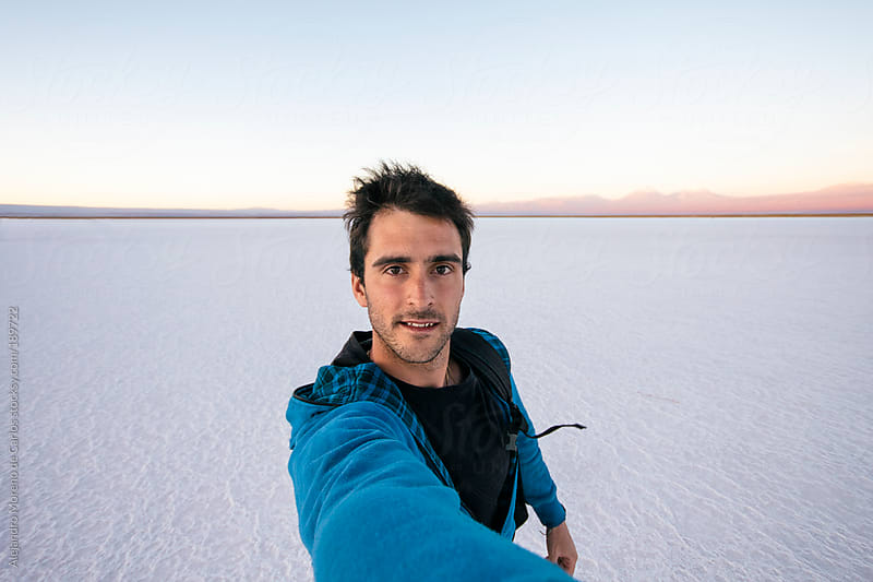 Young man selfie on a salt flat landscape in South America. Adventure travel by Alejandro Moreno de Carlos for Stocksy United