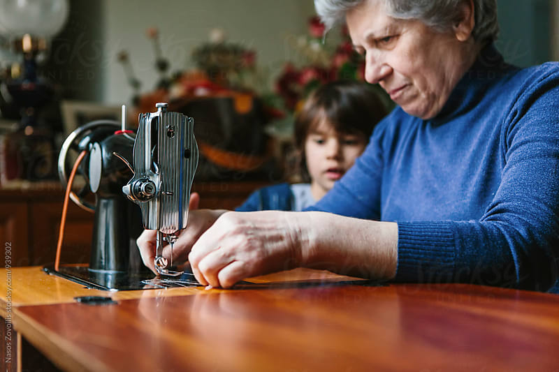 5 years old boy looking his grandmother working on a sewing machine by Nasos Zovoilis for Stocksy United