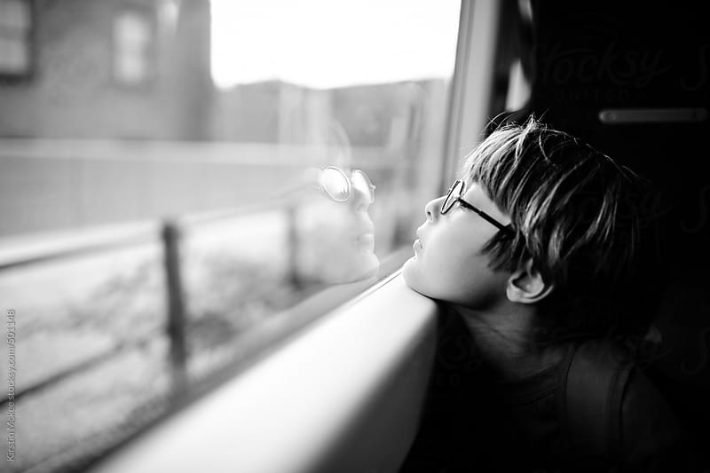 Boy looking out of a train window by Kirstin Mckee for Stocksy United