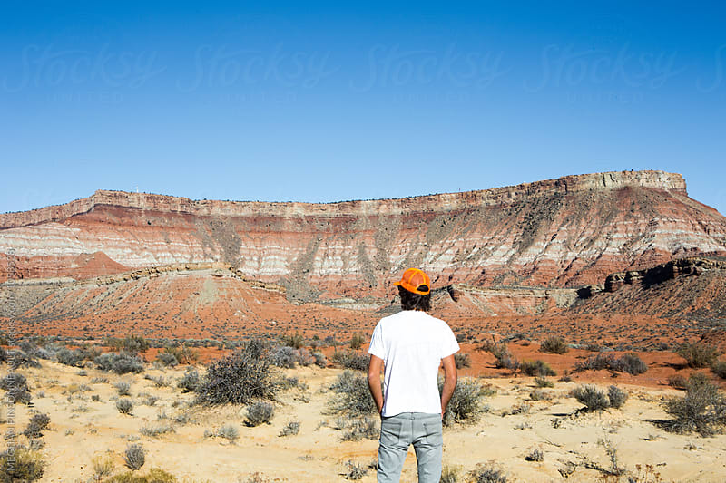 Man Looking Out at Amazing Desert Rock Formation by MEGHAN PINSONNEAULT for Stocksy United