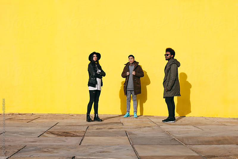 Group of multicultural friends standing in front of a yellow wall. by BONNINSTUDIO for Stocksy United