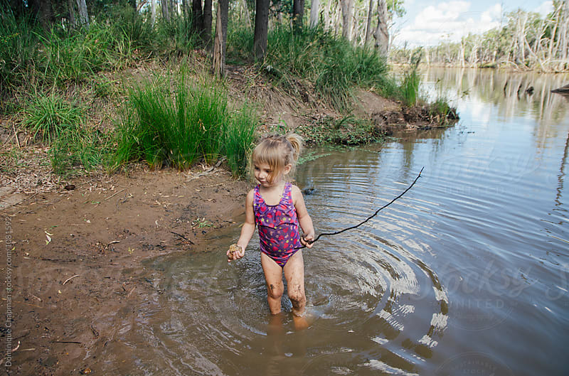 Young child playing in a lake with a stick by Dominique Chapman for Stocksy United