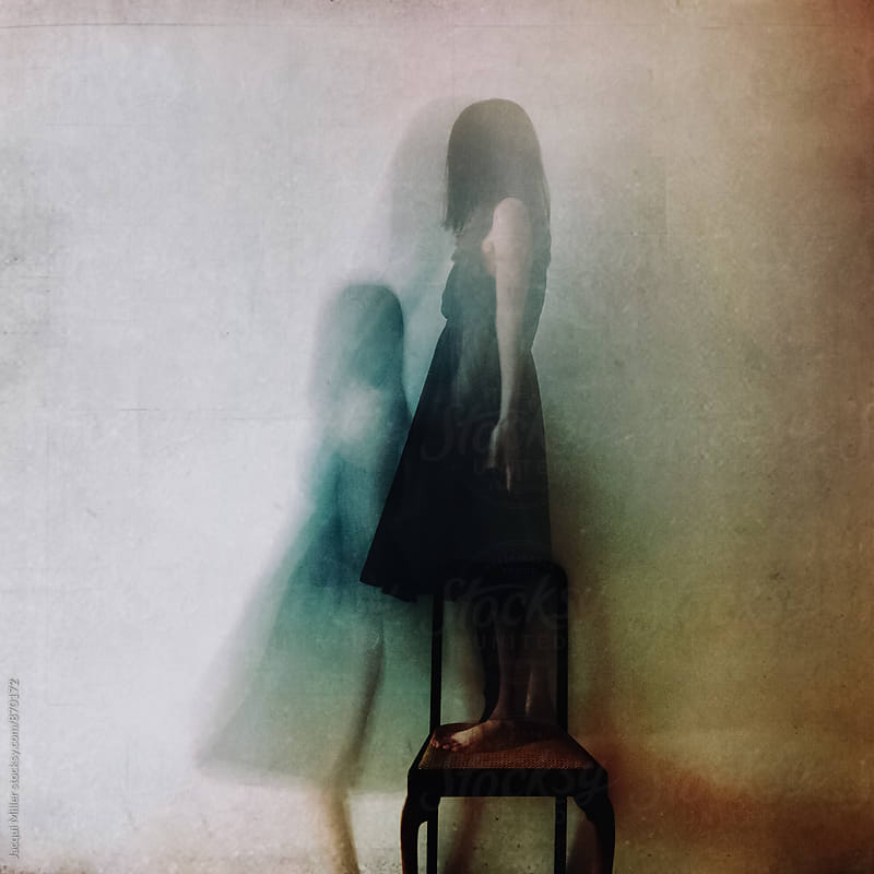Ghostly image of unrecognisable woman standing on a chair (heavily textured) by Jacqui Miller for Stocksy United