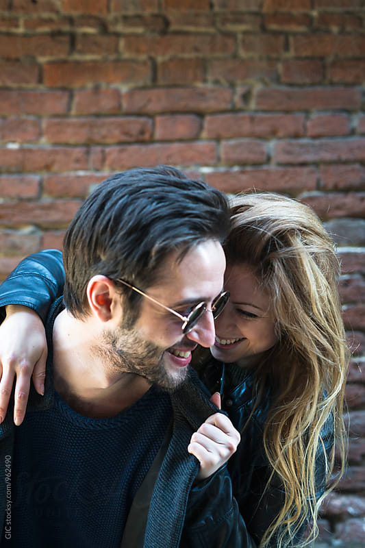Happy young couple in the city by Simone Becchetti for Stocksy United