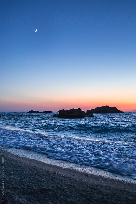 Crescent Moon over a Rocky Beach at Twililght by Helen Sotiriadis for Stocksy United
