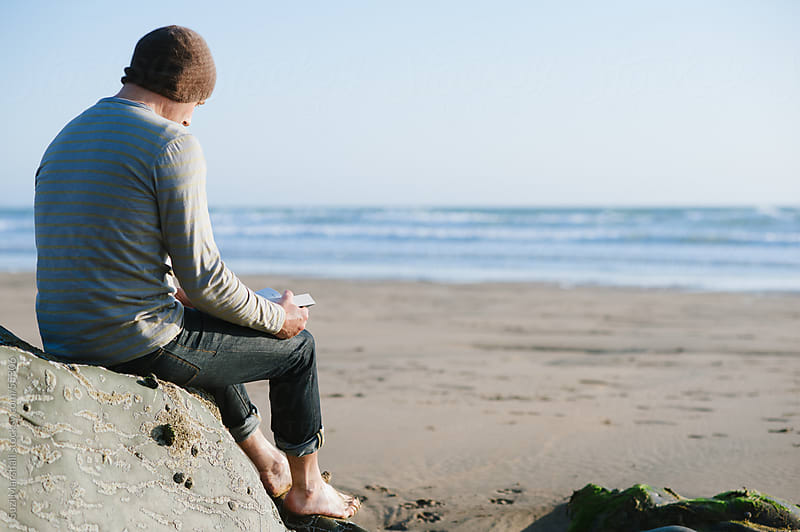 Man sat barefoot on a rock at the beach reading a book by Suzi Marshall for Stocksy United