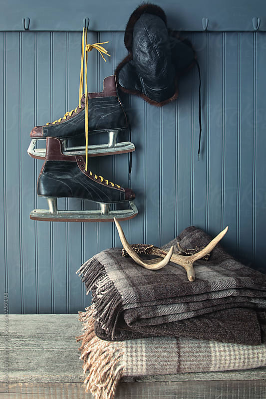 Men's vintage skates  hanging on hooks by Sandra Cunningham for Stocksy United
