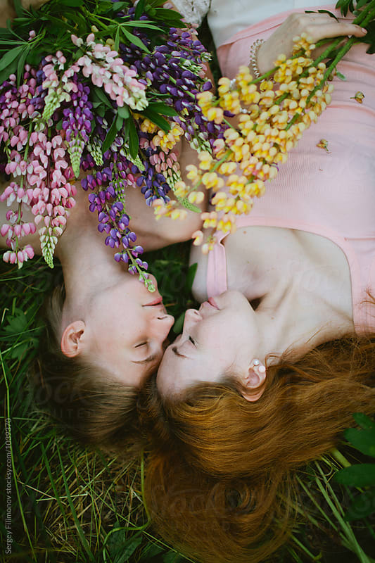 Two friends lying on green grass with flowers in hand by Sergey Filimonov for Stocksy United