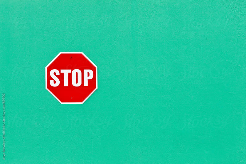 Image of a bright red stop sign against a vibrant green wall by anya brewley schultheiss for Stocksy United