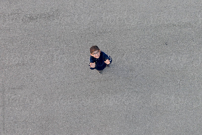 Looking Down At A Boy On The Ground by Ronnie Comeau for Stocksy United
