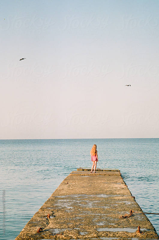 The girl on the pier. by Svetlana Shchemeleva for Stocksy United