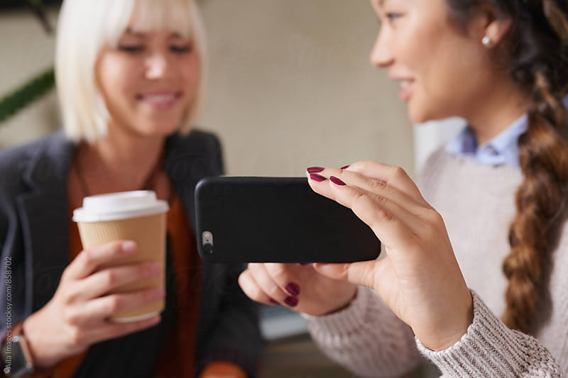 Stylish young women friends discuss social media on smart phone by Aila Images for Stocksy United