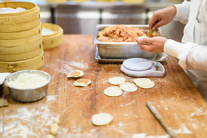 Professional cooks preparing dumpling by Lawren Lu for Stocksy United