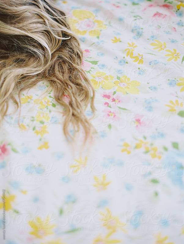 blonde hair on multi colored floral vintage sheets by wendy laurel for Stocksy United