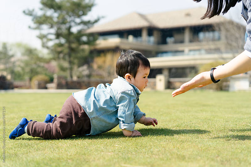 Baby boy crawling towards his mother on grass in a garden by Maa Hoo for Stocksy United