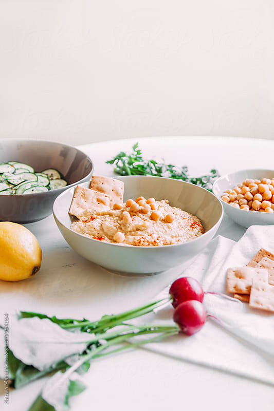 Hummus with cucumber salad  by Nataša Mandić for Stocksy United
