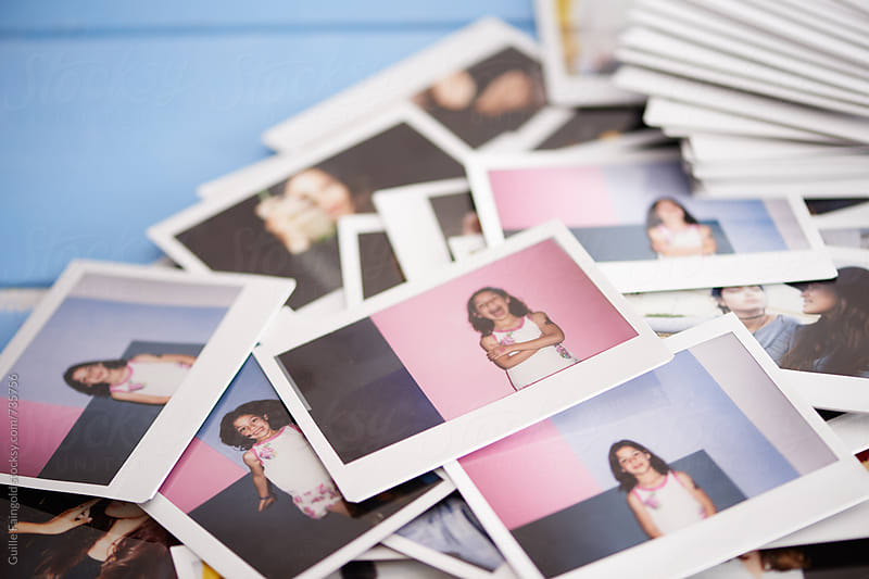 bunch of polaroids on a blue wooden table by Guille Faingold for Stocksy United