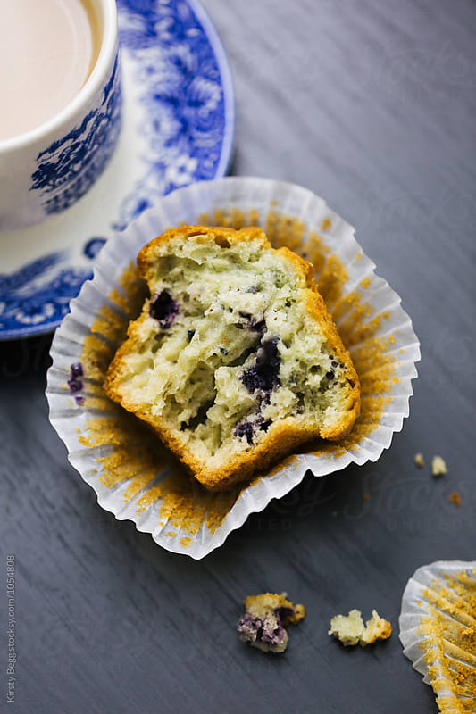Split open blueberry muffin with cup of tea by Kirsty Begg for Stocksy United