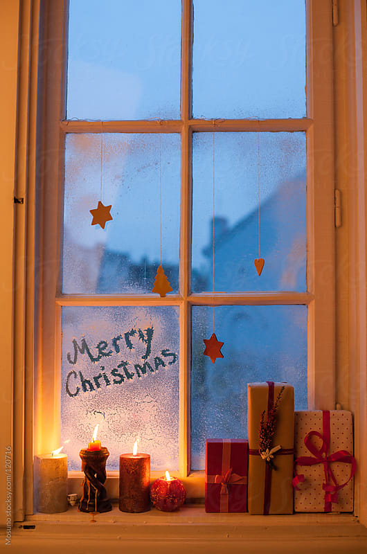 Burning Christmas Candles Next to the Window by Mosuno for Stocksy United