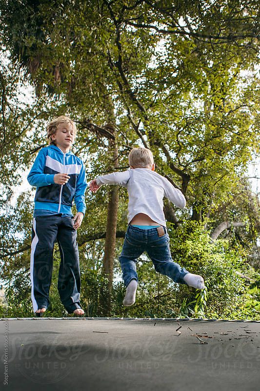 Boys jumping on trampoline by Stephen Morris for Stocksy United