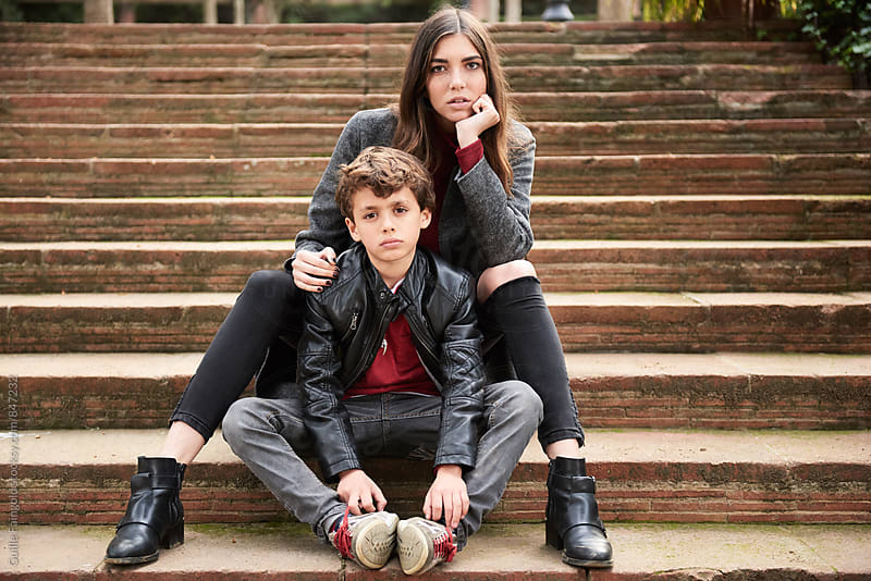 Sad boy and serious mother looking at camera while sitting on steps by Guille Faingold for Stocksy United
