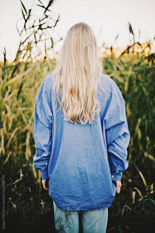 Young blonde girl walks in the evening at sunset by Sergey Filimonov for Stocksy United
