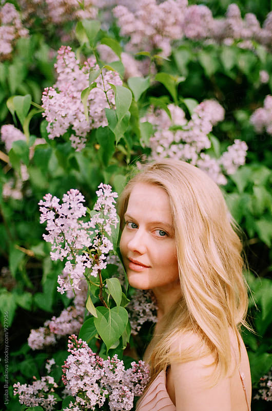 Portrait of a young woman among lilac in blossom by Lyuba Burakova for Stocksy United