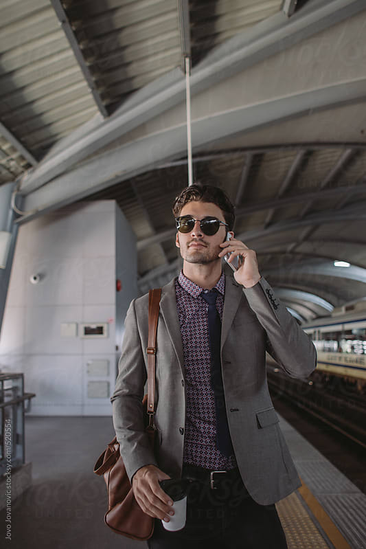 Young entrepreneur using his phone while waiting for a train by Jovo Jovanovic for Stocksy United