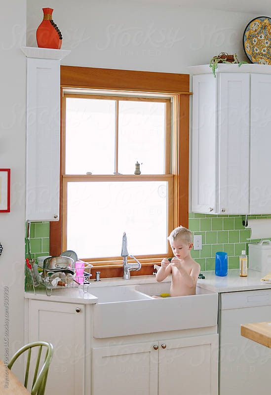 Child Taking Bath in Kitchen Sink by Raymond Forbes LLC for Stocksy United