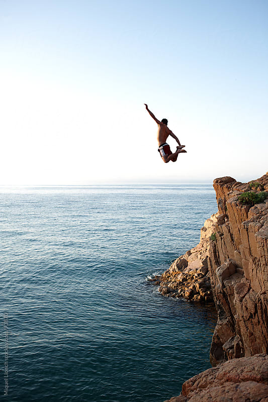 Young man jumping a cliff in a blue sea by Miquel Llonch for Stocksy United
