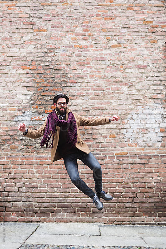 Happy man jumping in front of a brick wall by michela ravasio for Stocksy United