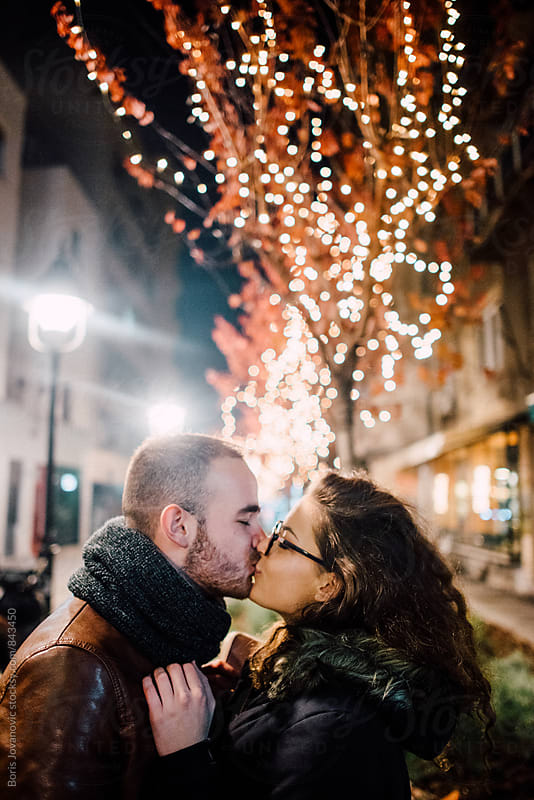 Couple having a romantic moment in front of the decorated tree by Boris Jovanovic for Stocksy United